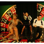 3 actors standing on the roulette wheel set look excitedly forwards.