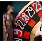 The woman in the sparkly dress stands at the side of the roulette wheel looking sad. We see a caption box in frame which reads: 'I hate this boat. It's a fucking jail'.