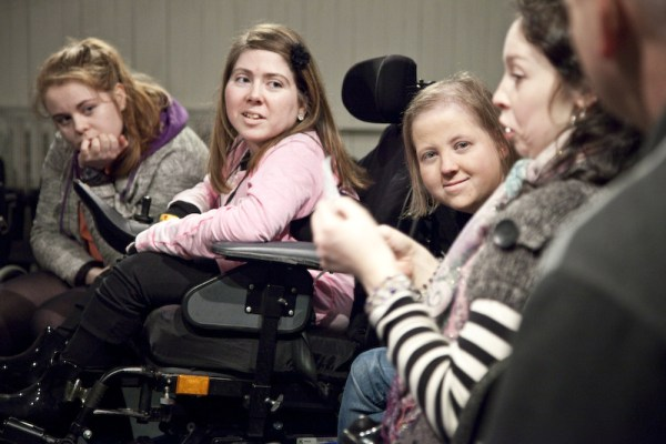 Four girls in wheelchairs, listening to an older one speak. they are very focused.
