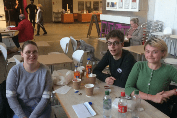 Three of the Youth Arts Consultants sit at a cafe table with empty cups of water bottles. Amy is on the left, while Jack and Poppy are on the right. They are all smiling at the camera.
