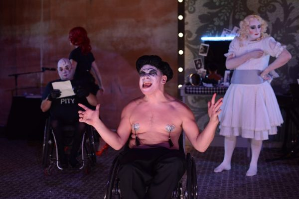 A shirtless man with a painted face wearing nipple tassles and a hat sits at the front of the stage and scowls. There are two more actors in drag makeup placed behind him..