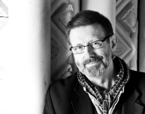 A black and white photo of Mike Kenny. He has a greying beard, thin framed glasses and is wearing a scarf.