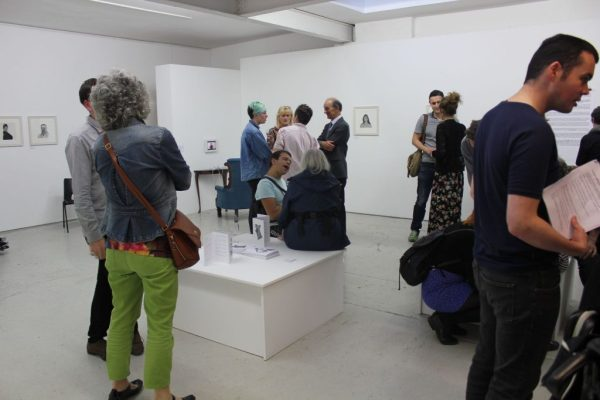 Clusters of people walk around an art gallery. The room looks really white and bright.