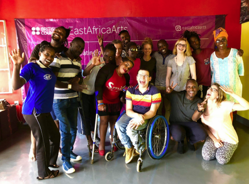 A group of 16 people are posing for a photo. The photo has been taken at a training session BOP was running in Rwanda for the British Council. Most of the people are black but there are four white people. One lady is using crutches and Robert from BOP is in his wheelchair, in the centre of the picture (how does he always manage that). Everyone is smiling and some people have their hands raised waving at the camera.