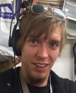 A photo of Nic Stuart. He has messy brown hair, a lip piercing and is wearing sunglasses on top of his head.