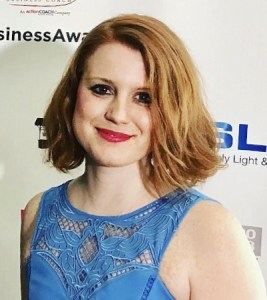 A photo of Claire McKenzie. She has medium length ginger hair and is wearing red lipstick.
