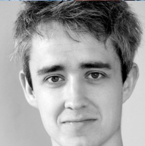 A photo of Gavin Whitworth. He has messy brown hair and thick eyebrows.