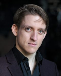 A photo of Matthew Duckett.He has brown hair, blue eyes and a strong jawline