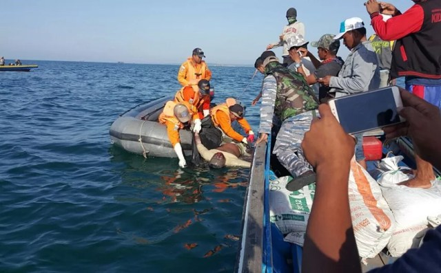 Indonesian rescue workers attempting to lift the body of a dead man onto the rescue boat on Thursday.