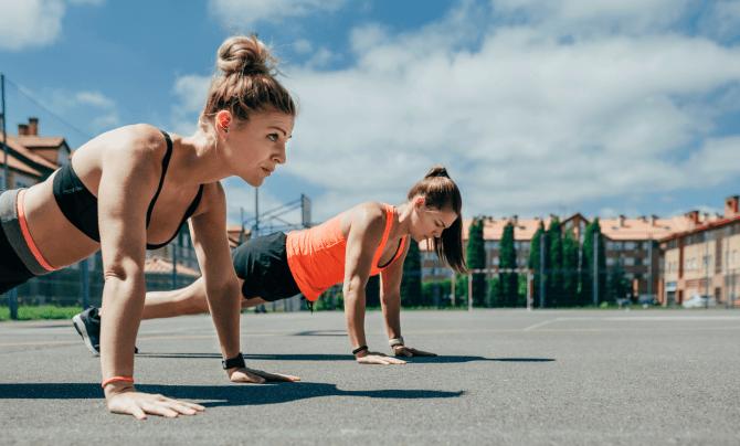 two women doing pushups outside