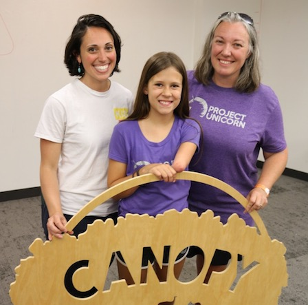 "Three people smile while holding a sign that says ""Canopy."""