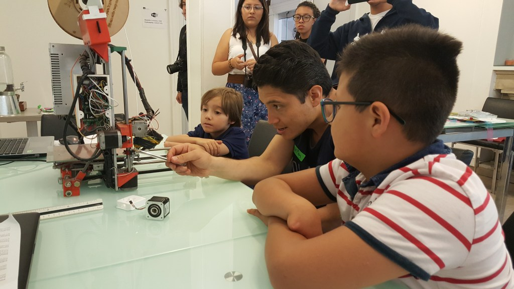 Kids work on a 3D printer with a volunteer at Fabrilab in Bogota