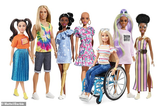 A collection of Barbie dolls include an Asian doll wearing long pigtails, a tall man with long blonde hair, a black doll with a gold prosthetic leg, a blonde doll in a wheelchair, a doll with long purple and green hair and a doll with vitiligo.