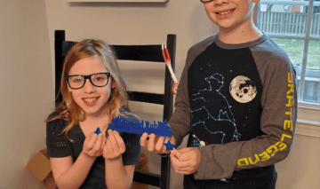 Abby and Robbie hold up the items they 3d printed after reading an article about Jordan