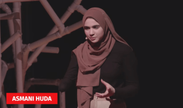 Asmani Huda speaks on stage and a graphic on the screen shows her name