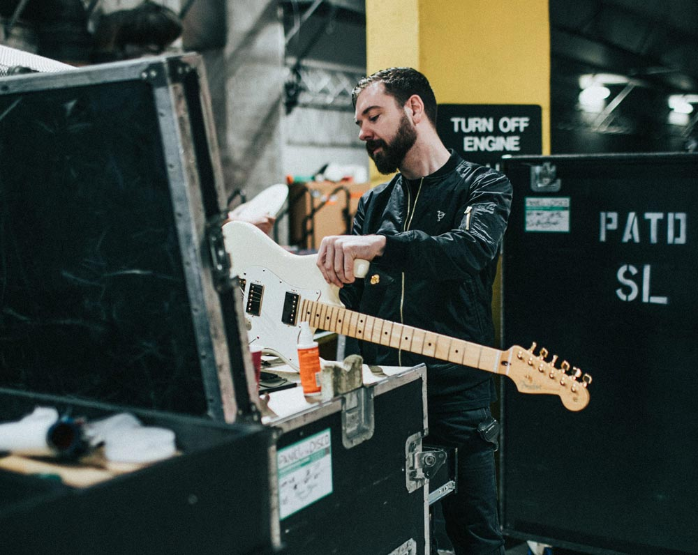 Kyle Henderson strings up a guitar before a Panic! at the Disco show.