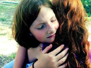 freckled girl hugging mother