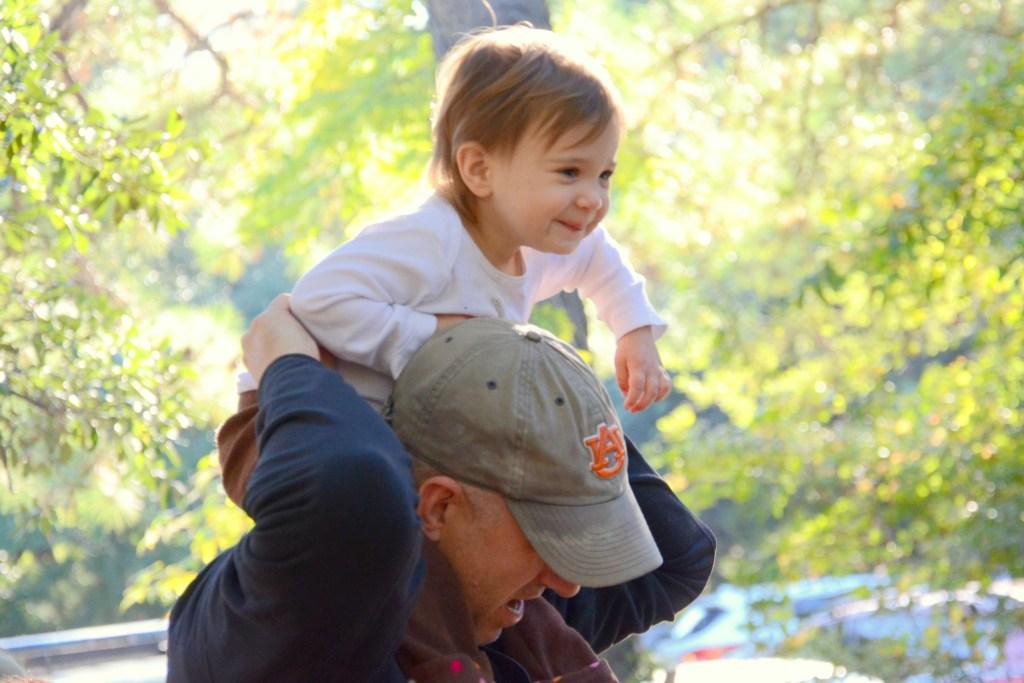 Happy child on dad's shoulders in sunlight