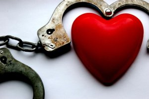 Love Hurts - red heart surrounded by rusty handcuffs