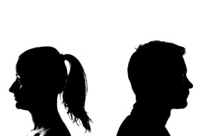 Couple at odds facing away in silhouette
