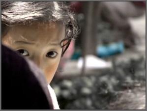 Anxious child hiding behind parent's shoulder