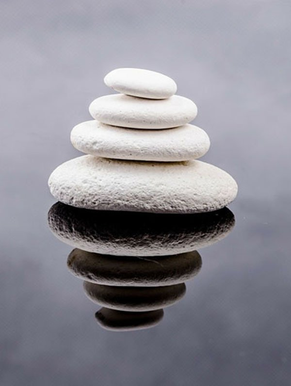 Tranquil stack of white stones and perfect reflection