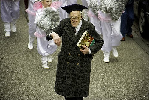 Elerly man dancing in street procession while wearing cap and gown