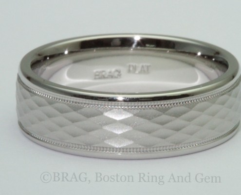Men's platinum wedding ring with diamond shaped pattern and mill grain edge details.