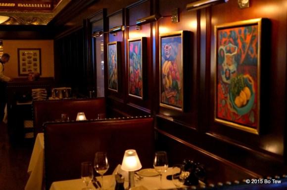Food paintings alongside cozy booths.