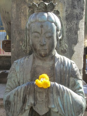 Beautiful yellow flower in the hands of a statue