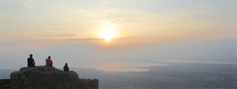 Fellow hikers enjoy the sunrise at the top of Masada