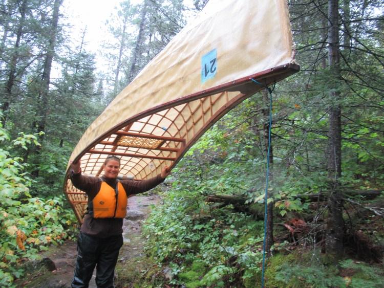 Ligeia portaging a canoe in the Boundary Waters Canoe Area (BWCA)