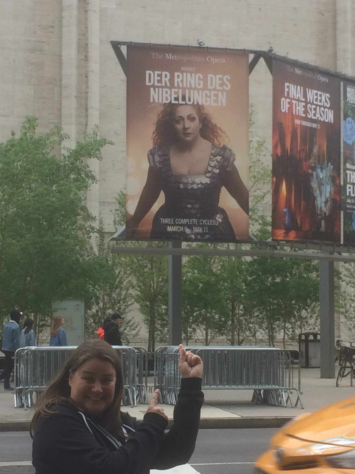 Standing and pointing at the billboard advertisement of the Ring at the Met