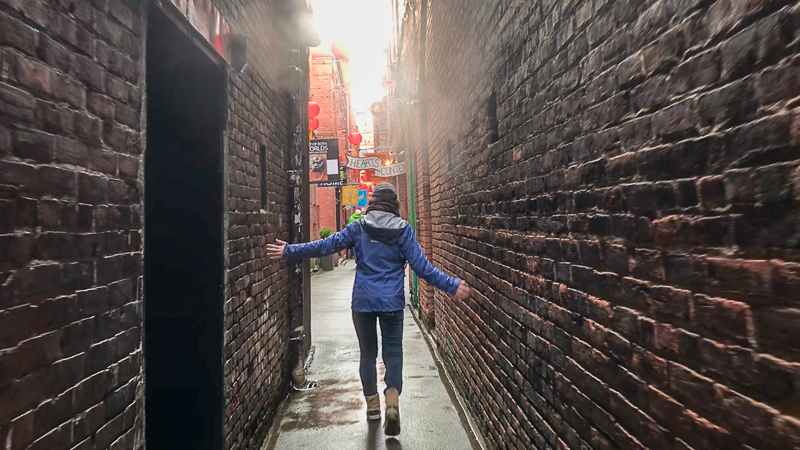 Angelina walking through Fan Tan Alley, the narrowest street in Victoria, British Columbia