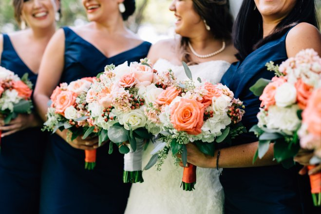 Bridesmaids in navy gowns with coral and ivory bouquets.