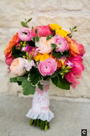Colorful bridal bouquet wrapped in vintage lace of mothers gown.