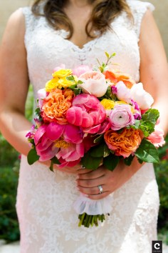 Bright colorful bridal bouquet including coral peony, orange roses and pink ranunculi.