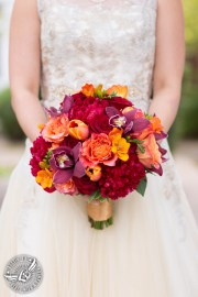 Raspberry peony, burgandy orchids and orange roses in a fall bridal bouquet.