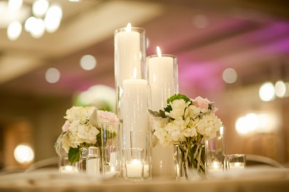 Ballroom tables adorned with candles and flowers.