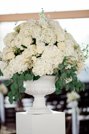 White hydrangea and roses flanking the aisle entrance.