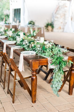 Vineyard table featuring lush foliage garlands.
