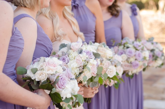 Lilac bridesmaids gowns accented with soft pastel bouquets.