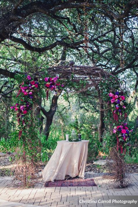 Sacred Oaks arbor decorated with lush jewel toned flowers