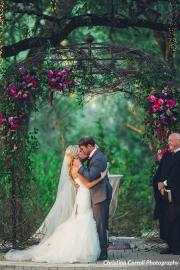 Outdoor ceremony at Sacred Oaks featuring jewel toned flowers