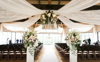 Indoor wedding ceremony at Omni Barton Creek pavillion with fabric draping and cascading smilax foliage.