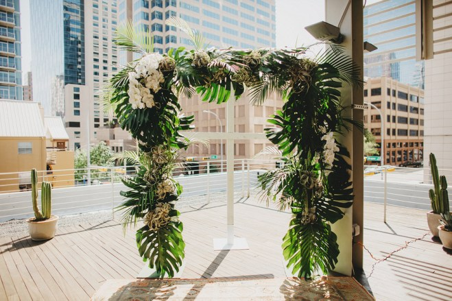 Wedding arbor with tropical leaves, tillandsia and phaelnopsis orchids.