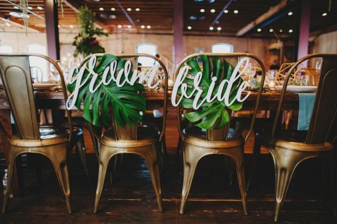 Laser cut bride and groom signs with monstera leaves.
