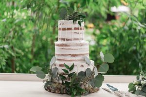 Nearly naked wedding cake with greenery accents.