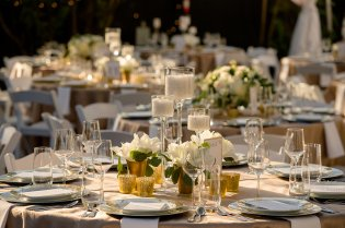Trio of candles with low all white flower centerpieces with gold accents.