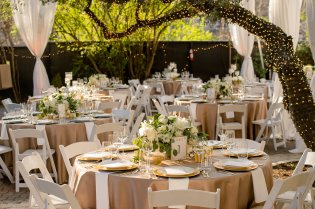 Dining table with low white flowers and gold tablecloths, white chairs and white napkins.